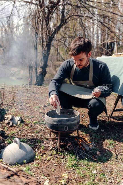 Cook in apron preparing lunch while putting pasty in boiling oil in pot on campfire