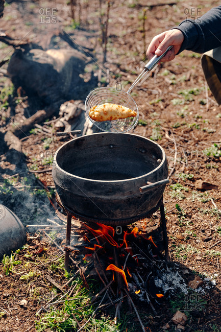 Unrecognizable cook preparing delicious pasty in boiling oil in pot on camping fire in countryside