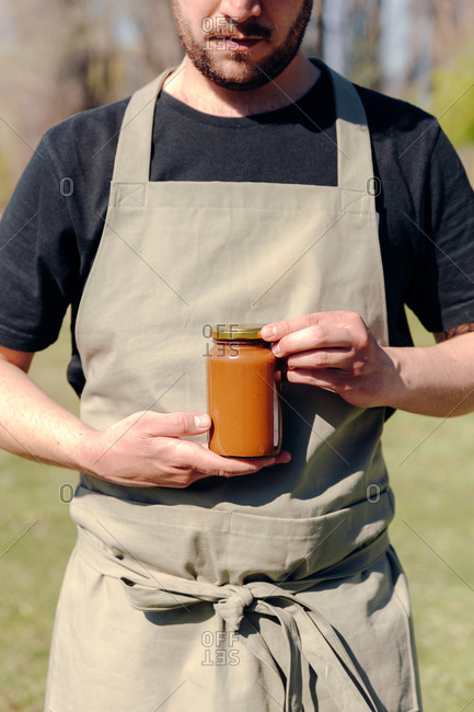 Unrecognizable crop male farmer standing in village with glass jar of tasty honey