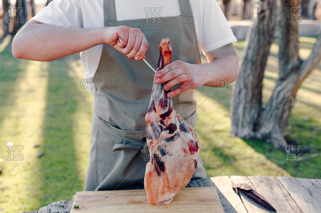 Anonymous male cook in apron standing at table in countryside with raw leg of lamb and preparing meat for hanging on metal hook