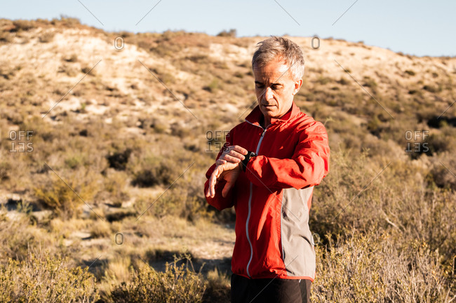 Concentrated middle aged male athlete in activewear checking time on smartwatch while standing in hilly terrain after workout