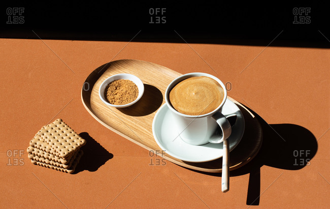 From above of ceramic cup of tasty coffee near crunchy crackers on wooden plate near bowl with cane sugar in cafe in sunlight