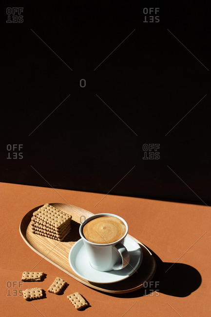 From above of ceramic cup of tasty coffee near crunchy crackers on wooden plate in cafe in sunlight