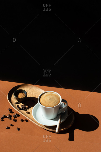 From above of ceramic cup of aromatic coffee with milk on wooden plate near bowl with cane sugar on table with shade in sunlight on black background