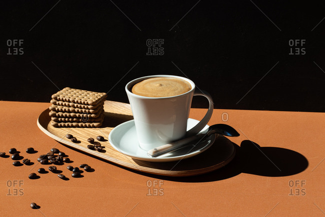 Ceramic cup of tasty coffee near crunchy crackers on wooden plate in cafe in sunlight and coffee grains