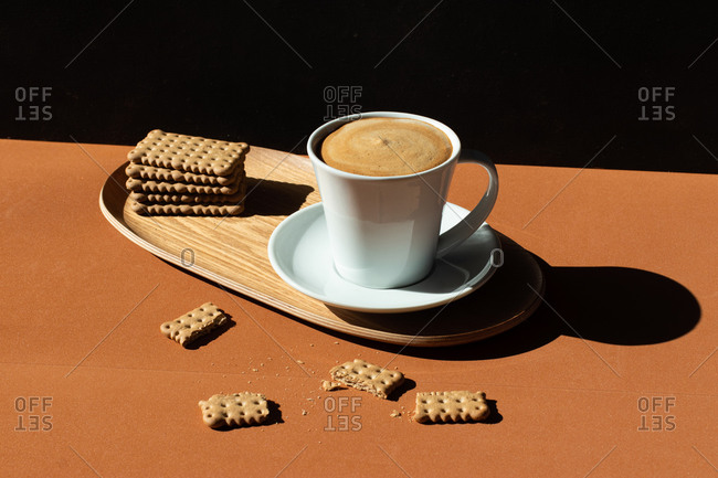 Ceramic cup of tasty coffee near crunchy crackers on wooden plate in cafe in sunlight