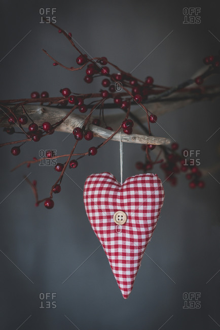 Soft textile checkered heart hanging on tree branch with decorative red berries on gray background in studio