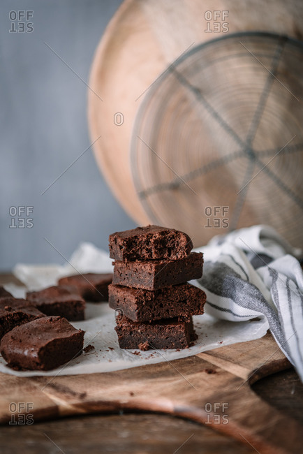 Yummy chocolate brownie pieces on cutting board on marble table at home
