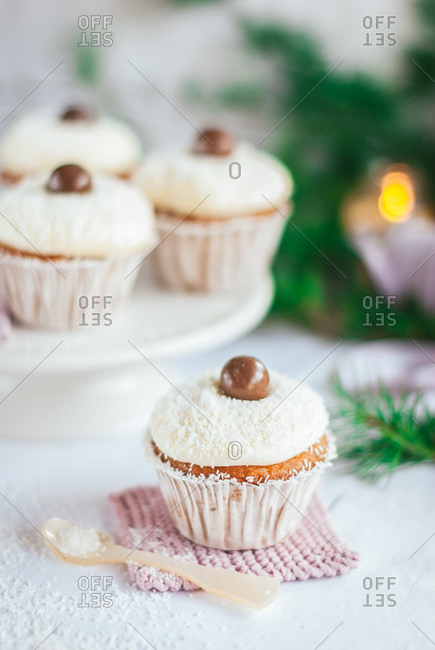 High angle of tasty cupcakes decorated with chocolate balls and sprinkled with coconut flakes placed on table for Christmas celebration