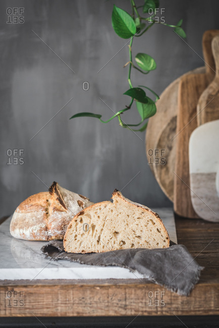 Cut loaf of fresh baked bread with crispy crust placed on marble tabletop in stylish kitchen