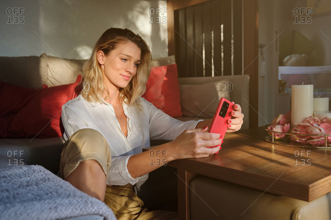 Optimistic young female in stylish outfit sitting on floor near sofa and browsing modern mobile phone at cozy home
