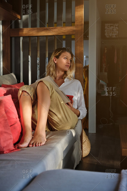 Full length barefoot contemplative female resting with notepad on comfy couch in modern interior and looking away pensively