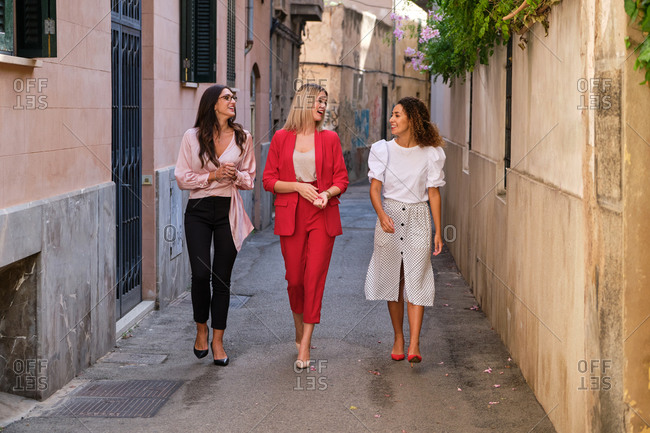 Full body female managers smiling and talking with each other while walking on narrow old street of town