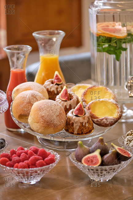 Buffet set with sweet pastry and mini burgers arranged near fresh fruits and berries on table with natural drinks in hotel restaurant