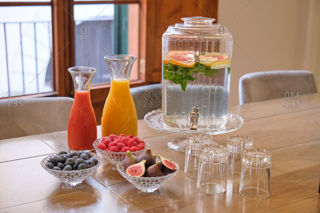 High angle of various fresh fruits and berries in bowls placed near bottles with juice and infused water served on wooden table in meeting room