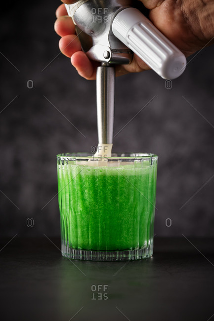 Crop faceless bartender adding foam to fresh green lime cocktail in glass served on black counter