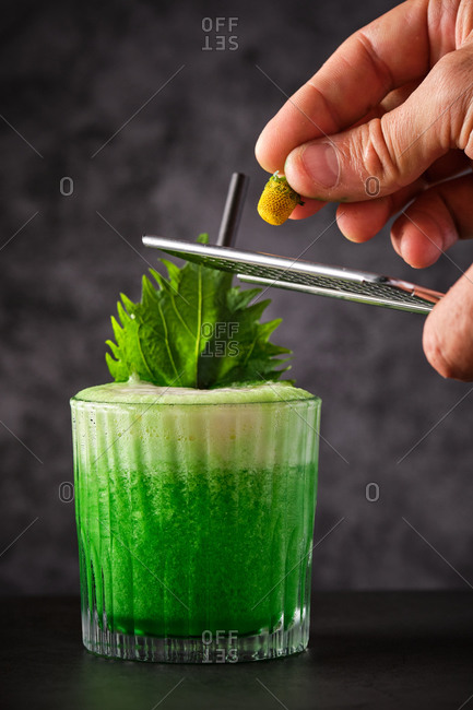 Crop unrecognizable bartender grating citrus zest on green cocktail decorated with fresh mint leaves and served on black table