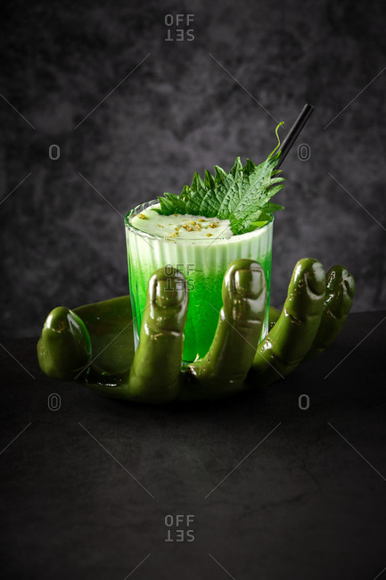 High angle glass of refreshing green smoothie with foam and leaf served on creative hand shaped vase