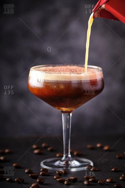 Side view glass of tasty foamy coffee liquor decorated with chocolate and served on black table among scattered beans
