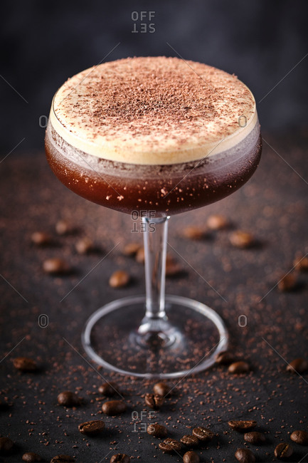 From above glass of tasty foamy coffee liquor decorated with chocolate and served on black table among scattered beans