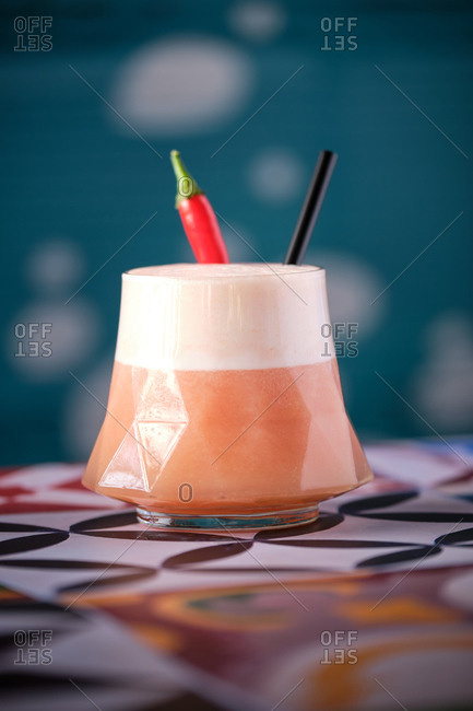 Glass of tasty exotic cocktail with froth served in geometric glass and decorated with chili pepper and straw