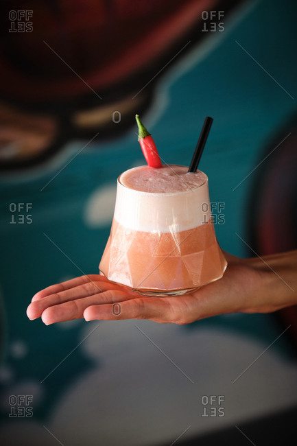 Crop anonymous bartender holding glass of fresh foamy drink decorated with straw and chili pepper