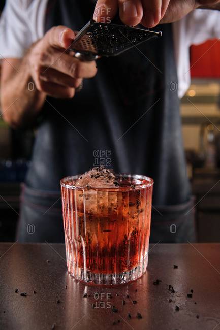 Unrecognizable crop bartender garnishing alcohol cocktail in glass with grated chocolate while working in bar