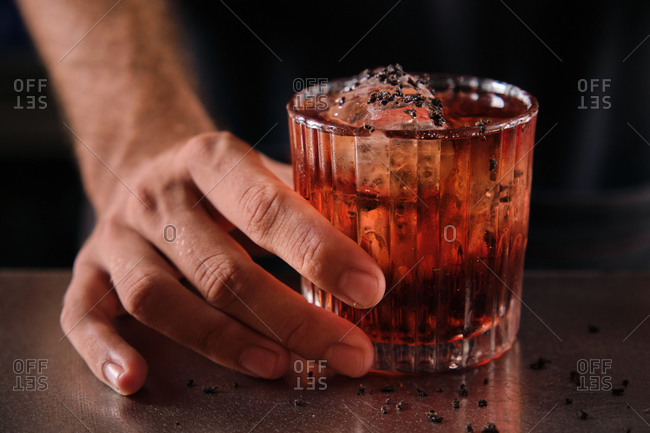 Closeup of unrecognizable barman at counter with glass of alcohol cocktail with ice cubes garnished with grated chocolate in bar