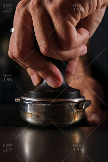 Closeup of crop faceless barista standing at counter and pressing coffee in portafilter while preparing delicious beverage