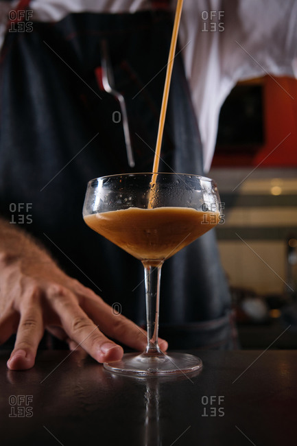 Low angle of crop bartender pouring coffee in glass while preparing refreshing cocktail in bar
