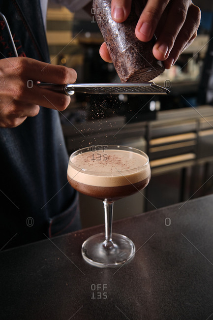 Crop anonymous bartender decorating Martini cocktail with coffee with grated chocolate while standing at counter in bar