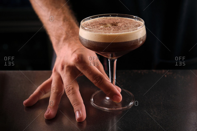Closeup of anonymous barkeeper with glass of Martini with coffee and chocolate placed on counter in bar