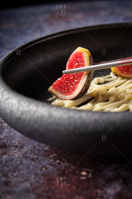 Closeup of faceless person taking figs with chopsticks while having lunch in luxury restaurant