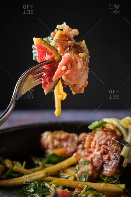Closeup of savory pig trotter with fruits and vegetables on fork in luxury restaurant on black background