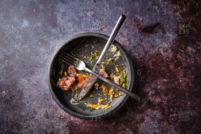 Top view of empty dirty plate with dish leftovers and metal utensils placed on table in restaurant after dinner