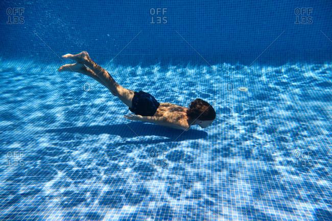 Underwater shot full body energetic teenage boy in swimming trunks diving into clean pool water in resort