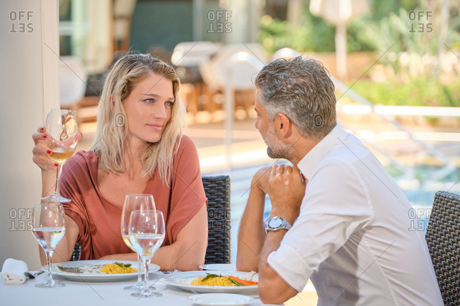 Attractive blond haired wife in dress looking at husband with love while having dinner in cafe near swimming pool in sunlight
