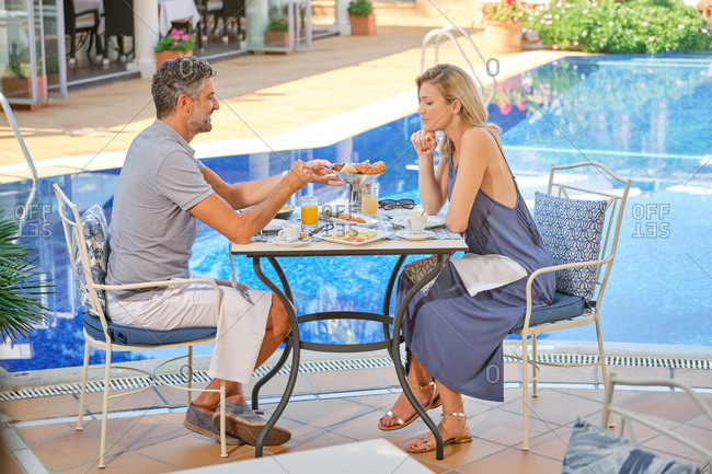 Attractive couple man and woman having dinner in cafe near swimming pool in sunlight