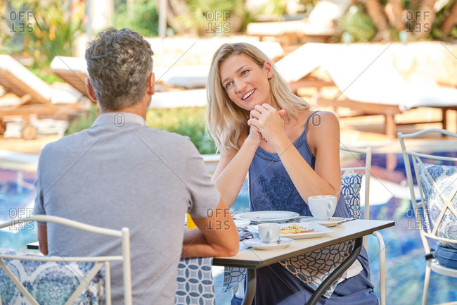 Cheerful blond haired wife in dress looking at husband with bright toothy smile while having dinner in cafe near swimming pool in sunlight