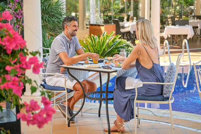Cheerful blond haired wife in dress looking at husband with smile while having dinner in cafe near swimming pool in sunlight
