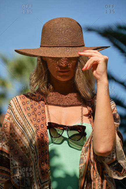 Serious young blond haired slim female tourist touching hat with eyes closed while lounging in sunlight under blue cloudless sky