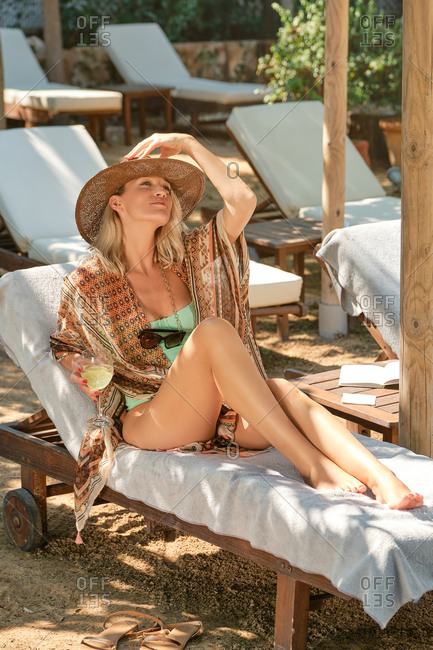 Full body of young stylish slim female traveler in swimsuit and hat looking away with half smile while lounging on deckchair and drinking alcoholic beverage in yard of hotel