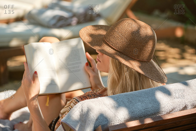 Back view young beautiful female traveler in hat reading book while lounging in yard of hotel in sunlight