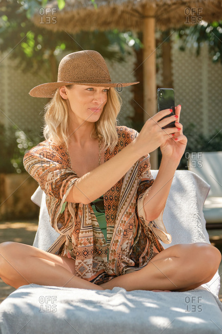 Gorgeous young female traveler in stylish summer outfit and straw hat sitting on sunbed on sandy beach and using smartphone on sunny day