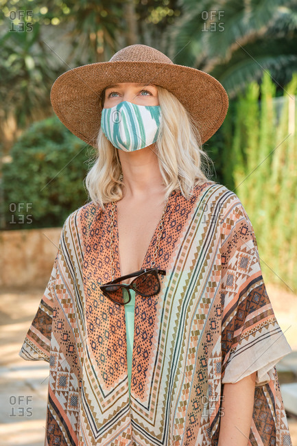 Unrecognizable young female traveler in trendy summer outfit and straw hat wearing face mask while standing in tropical garden during coronavirus