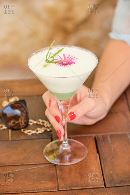 Crop female tourist with bright red manicure drinking cocktail at wooden table on blurred background