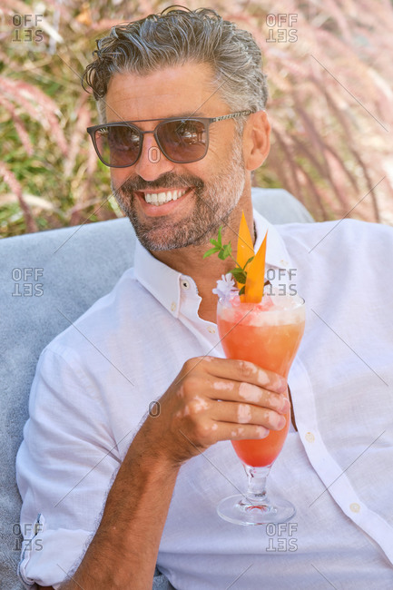 Happy bearded adult male tourist in white shirt and sunglasses enjoying delicious exotic fruit smoothie while relaxing on sunbed in tropical garden