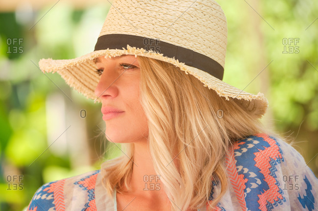 Dreamy young female traveler with blond hair in trendy straw hat and sundress enjoying summer holidays in green garden and looking away