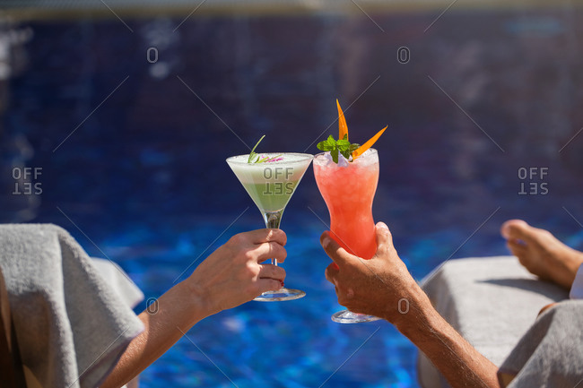 Crop anonymous male and female travelers relaxing on deckchairs near swimming pool with exotic colorful cocktails during summer holidays