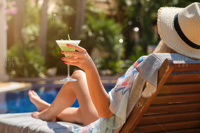 Side view of unrecognizable female tourist in sundress and straw hat drinking refreshing cocktail while sunbathing on deckchair near swimming pool